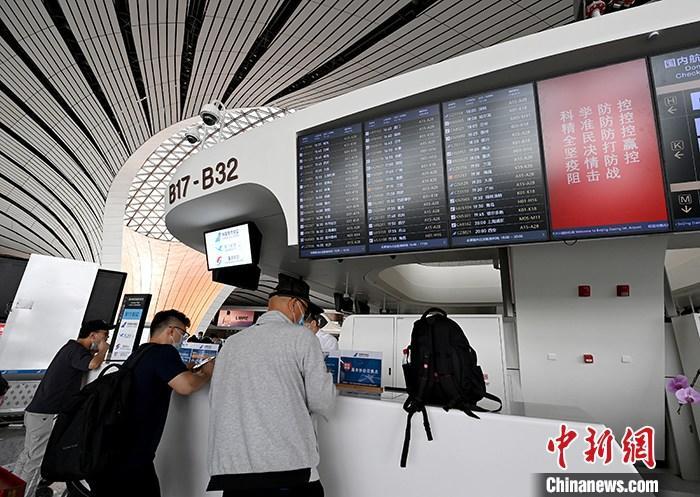6月3日,旅客在北京大兴国际机场出发层咨询航班信息。自6月1日起,大兴机场国内航班开始逐步恢复。 中新社记者 侯宇 摄