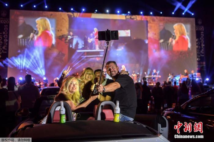 当地时间6月2日,雅典南部郊区Glyfada的驾车节的开幕之夜,民众驾驶汽车前往举办地,在车中欣赏表演。图为前往参加开幕之夜的观众合影留念。