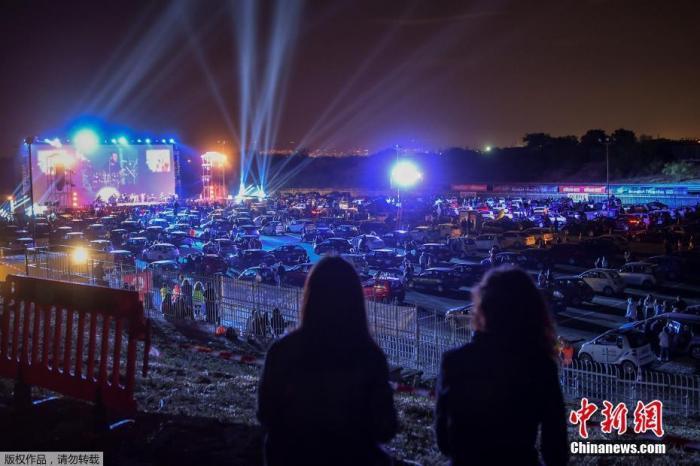 当地时间6月2日,雅典南部郊区Glyfada的驾车节的开幕之夜,民众驾驶汽车前往举办地,在车中欣赏表演。图为驾车节开幕之夜上的音乐表演。