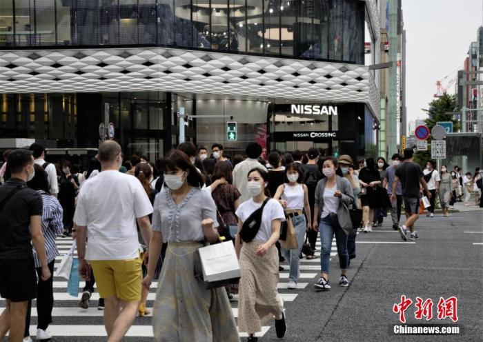 """当地时间6月6日,日本东京都发布新冠肺炎疫情""""东京警报""""后的首个周末,当地选择出门逛街的民众数量并没有大幅减少。图为当地民众佩戴口罩走过东京街头。 /p中新社记者 吕少威 摄"""