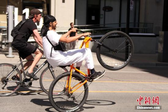 People play with their bicycles on a street in Toronto, Canada, June 6, 2020. (Photo/China News Service)
