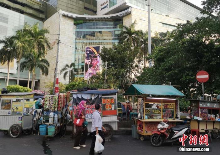 资料图:当地时间6月8日傍晚,印尼首都雅加达市中心一个豪华购物商场外,小商贩们在摊位上等待客人。 <a target='_blank'  data-cke-saved-href='http://www.chinanews.com/' href='http://www.chinanews.com/'>中新社</a>记者 林永传 摄