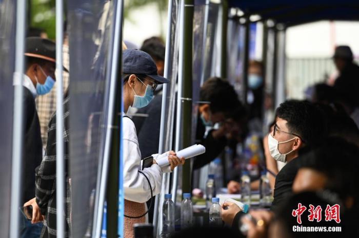资料图:求职者与用人单位工作人员交流洽谈。中新社记者 何蓬磊 摄