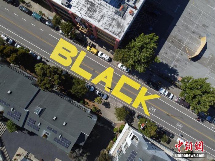 """当地时间6月13日,美国旧金山市政厅附近的街面上,出现用黄油漆涂写的巨幅""""Black Lives Matter""""(黑人的命也是命)字样。由美国明尼苏达州白人警察暴力执法致非洲裔男子乔治・弗洛伊德死亡一事在美国引发的全国性示威活动已持续多日,相关壁画、字样也出现在美国多地。 中新社记者 刘关关 摄"""