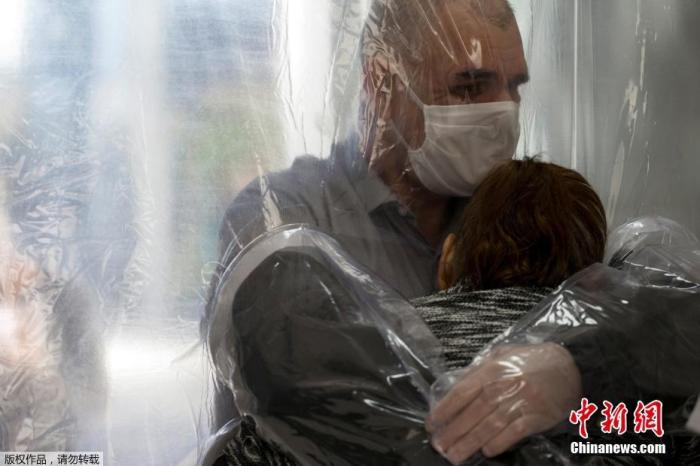 近日,巴西圣保罗,奥西玛·席尔瓦在养老院隔着半透明的塑料窗帘拥抱了85岁的母亲卡梅丽塔·瓦尔弗德(Carmelita Valverde)。 拉美地区新冠肺炎疫情持续发展。巴西仍是该地区疫情最严重的国家,确诊病例数逾85万,累计死亡病例42720例。专家预计,巴西疫情仍处上升期,预计峰值可能7月才会到来。