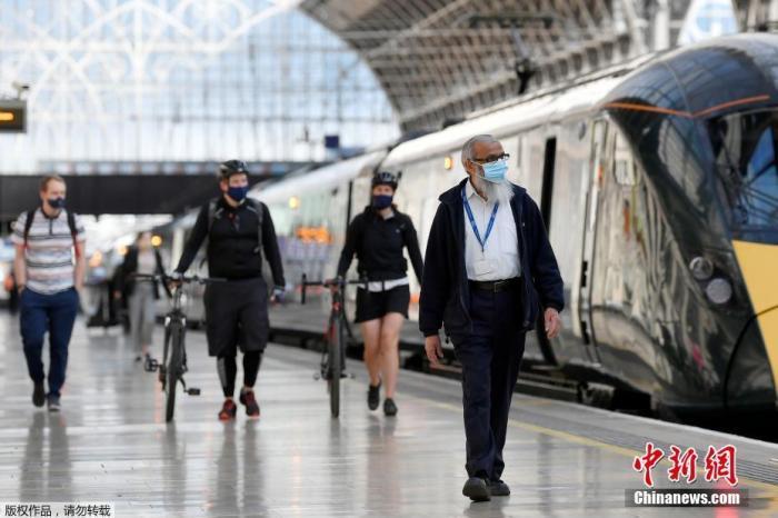 当地时间6月15日,英国伦敦,戴着口罩的通勤者到达帕丁顿车站。