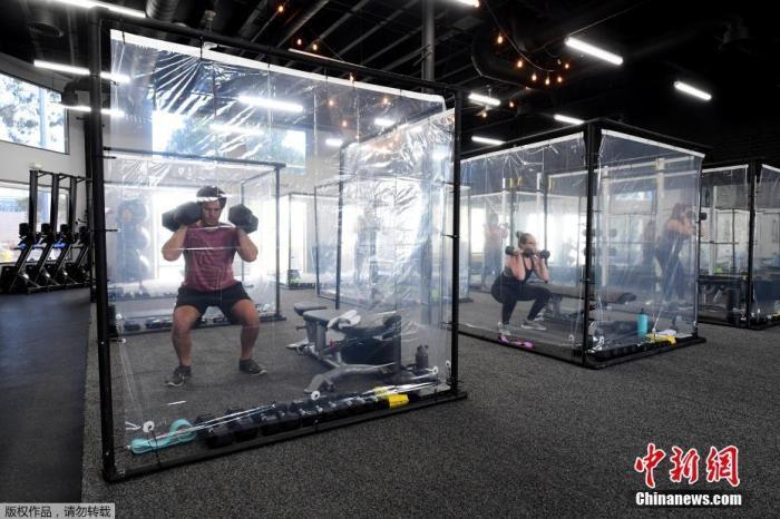 當地時間2020年6月15日,美國加州雷東多海灘,當地一健身中心重開,學員在塑料健身艙里健身,保持社交距離。
