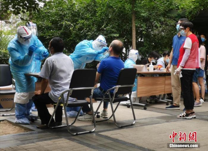 6月17日,北京西城一实走封闭管理的社区,做事人员为社区居民进走核酸检测。中新社记者 杜洋 摄