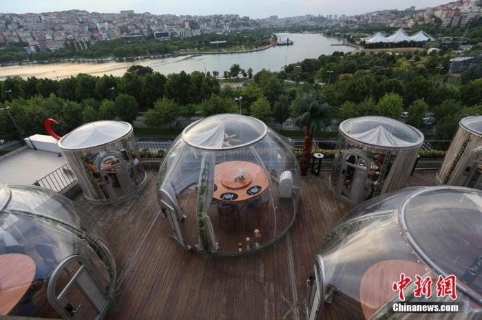 """当地时间2020年6月16日,土耳其伊斯坦布尔,为保持用餐期间""""社交距离"""",一家餐厅设置了""""圆顶""""形状的隔离用餐区。土耳其从6月1日起解除一系列新冠肺炎疫情防控措施。 图片来源:视觉中国"""
