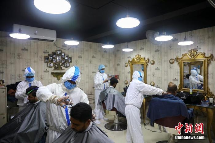 当地时间6月16日,孟加拉国达卡,理发师穿着防护服为顾客理发。
