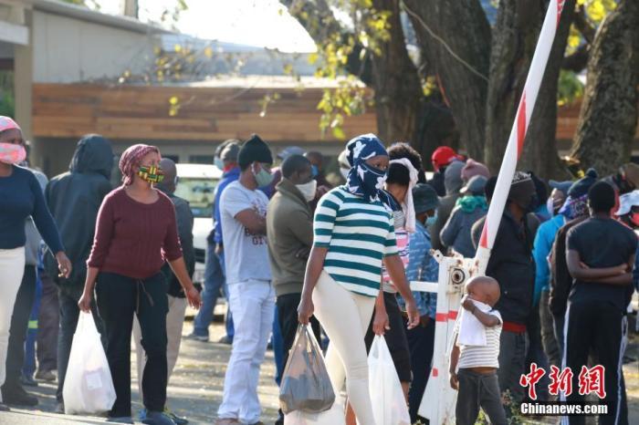 进入六月以来,南非新冠肺炎疫情呈现快速增长态势。日前,<a target='_blank' href='http://www.chinanews.com/'>中新社</a>记者走上南非街头,探访南非民众在疫情下的生活。图为在南非约翰内斯堡一社会救济站,南非低收入民众领取政府发放的救济食品。 <a target='_blank' href='http://www.chinanews.com/'>中新社</a>记者 王曦 摄