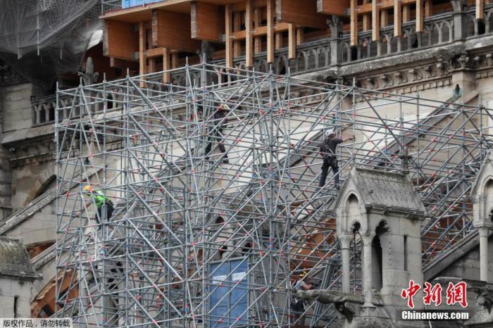 资料图:当地时间2020年6月17日,法国巴黎,工人拆除巴黎圣母院被烧毁的脚手架,并安装新的脚手架。