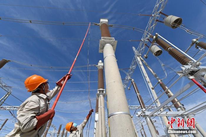 资料图:运维人员在进行停电、验电、挂接地线作业。 确·胡热 摄