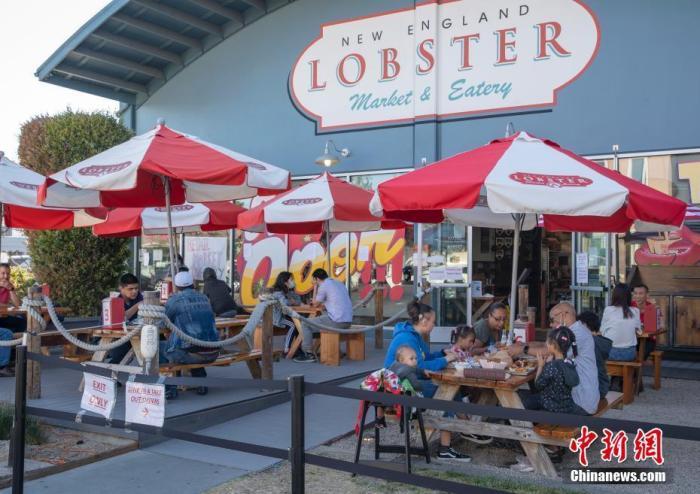 当地时间6月19日,美国加利福尼亚州圣马特奥县居民在一家餐厅就餐。目前,加州重启经济进入第三阶段,只要所在县允许,电影院、餐厅以及大型购物中心等高风险设施可以重新营业。 记者 刘关关 摄