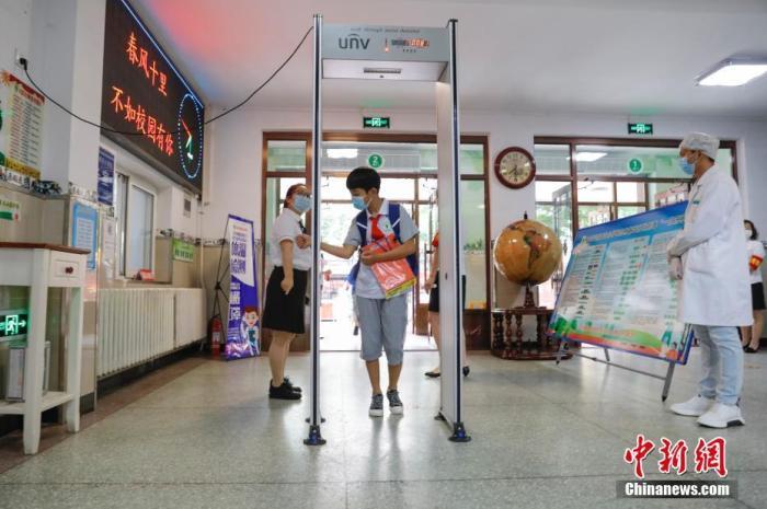 资料图:6月20日,黑龙江省哈尔滨市小学毕业年级迎来复课第一天。图为学生们通过测温门。中新社记者 吕品 摄