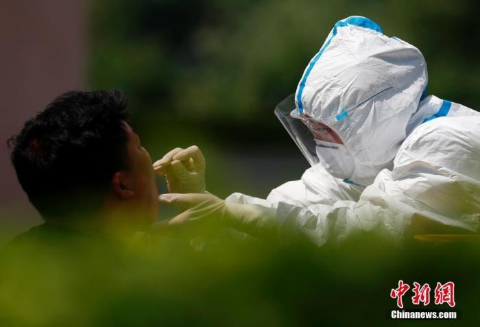 6月20日,北京市东城区居民进行核酸检测。中新社记者 富田 摄