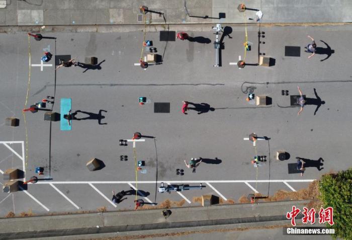 """当地时间6月20日,美国加利福尼亚州马林县圣安塞尔莫一家健身房在门口的道路上重新营业,民众在保持""""社交距离""""的前提下健身。记者 刘关关 摄"""