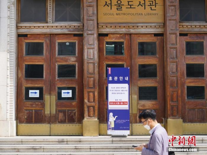 6月23日,一位韩国首尔市民经过首尔市立图书馆门前,该图书馆贴出闭馆通知。近来,包括韩国首尔、仁川、京畿道在内的首都圈确诊病例持续增加。 <a target='_blank' href='http://www.chinanews.com/'>中新社</a>记者 曾鼐 摄