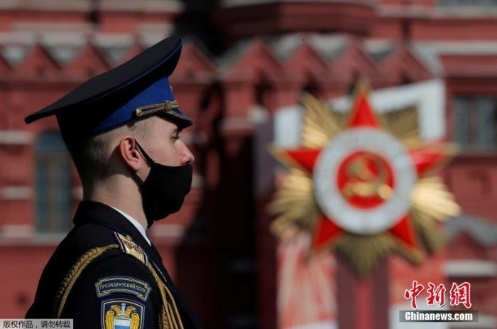 据悉,今年的阅兵式将还原1945年阅兵式的场景,退伍老兵也将参加。图为阅兵开始前,俄罗斯军人带着口罩站在街头。
