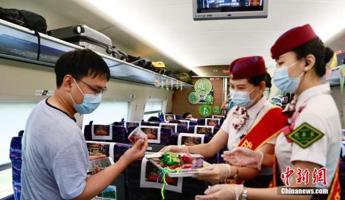 6月25日,成都东开往万州北的G8781次列车上,列车长邀请旅客一起制作艾叶香包。 陶静 摄