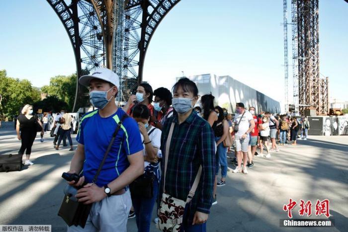 当地时间2020年6月25日,法国巴黎,埃菲尔铁塔部分重新开放,游客戴口罩参观。因疫情被迫关闭三个月的埃菲尔铁塔于本月25日重新对外开放,但是禁止使用轿厢电梯,游客必须徒步登塔。