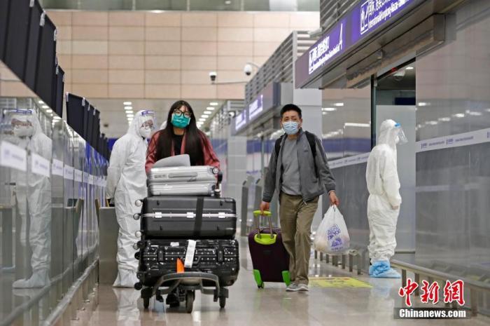 资料图:旅客推着行李抵达机场。 殷立勤 摄
