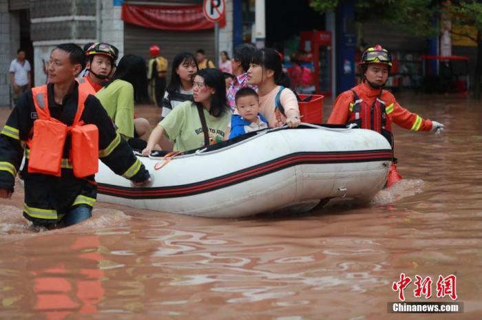 资料图:消防救援人员紧急转移洪涝灾害被困群众。 肖乐峰 摄