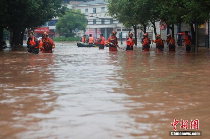 资料图:消防救援人员紧急转移洪灾被困民众。 肖乐峰 摄