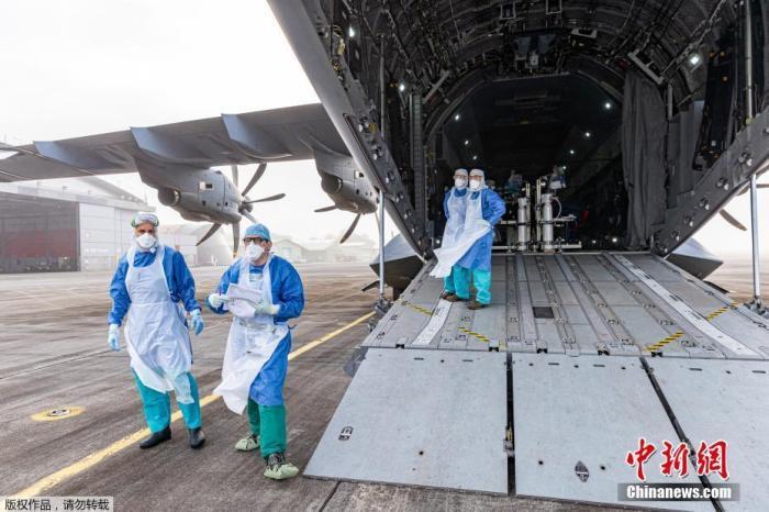 当地时间6月28日,法国海外省法属圭那亚空军基地,医务人员在军用运输机空客A400M中等待将新冠肺炎患者疏散到法属西印度群岛的医院。