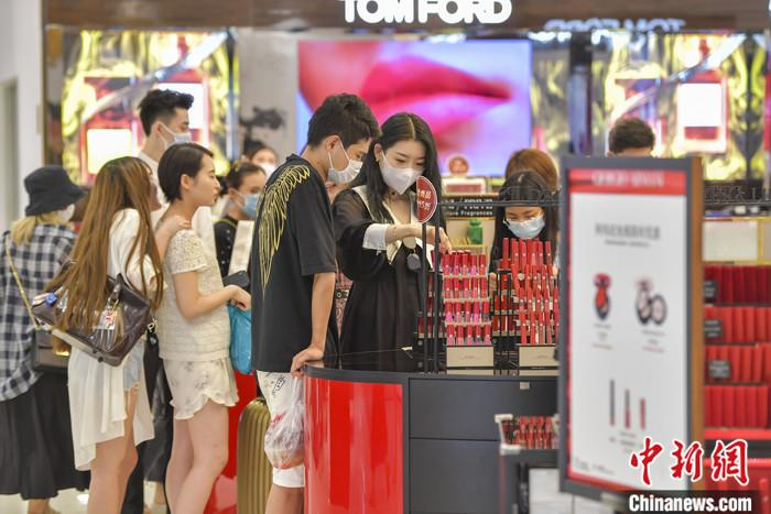 资料图:游客在海口日月广场免税店选购化妆品。中新社记者 骆云飞 摄