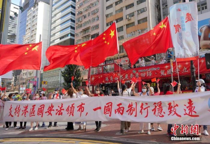 """6月30日下午。一众香港市民来到铜锣湾街头举行""""支持港区国安法唱国歌""""活动。大家挥舞五星红旗和香港区旗,高唱国歌与《我和我的祖国》等爱国歌曲,赢得街头市民的阵阵掌声。图为支持国安法的市民与""""港岛各界庆香港回归、贺国安立法""""巡游巴士在铜锣湾街头相遇。 记者 张炜 摄"""