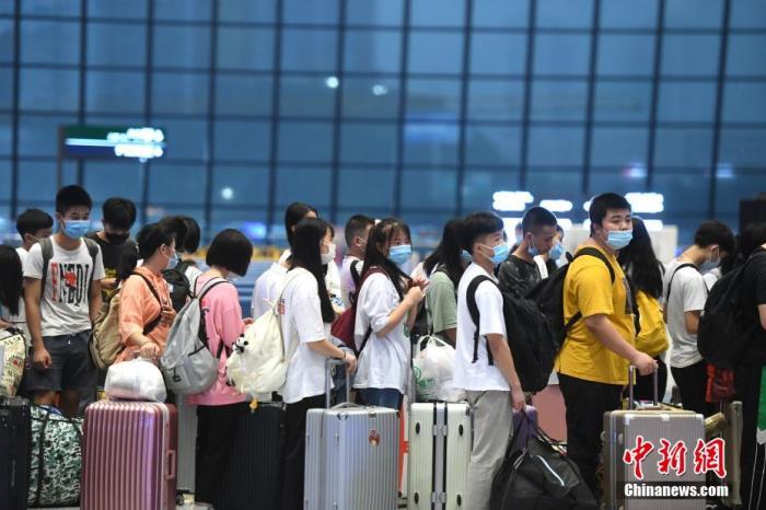 7月1日,旅客在重庆火车西站出行。当日,为期62天的中国铁路暑运正式拉开帷幕,至8月31日结束。图为旅客排队检票。 陈超 摄