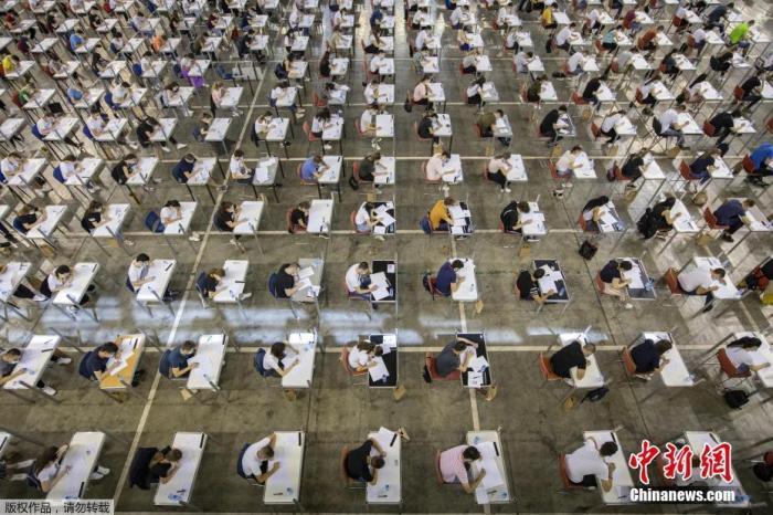 当地时间6月30日,塞尔维亚贝尔格莱德,学生们在博览会大厅里参加大学入学考试。