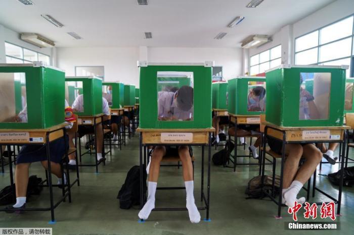 当地时间2020年7月1日,泰国巴吞他尼府,学校恢复上课,把旧投票箱放在课桌上帮助学生保持社交距离。