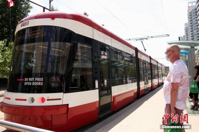 当地时间7月3日,当地市民佩戴口罩在加拿大多伦多等候搭乘电车。多伦多公共交通局自7月初起施行防疫新规,强制要求所有公共交通工具乘客佩戴口罩。 中新社记者 余瑞冬 摄