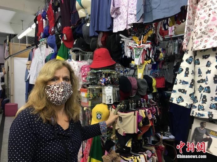 内地时间7月3日,巴西圣保罗,一位女东家戴口罩开门营业。 /p平心在线记者 莫成雄 摄