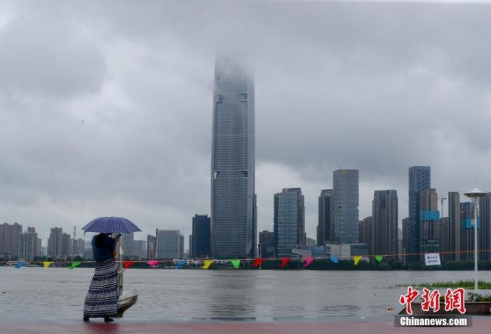 7月5日,湖北武汉,市民在汉口江滩边观水。受长江上游持续强降雨及汉江中上游来水的影响,长江、汉江武汉段的水位继续上涨。中新社记者 张畅 摄