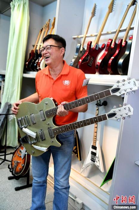 图为6月29日,吕孟哲展示其公司生产的特色吉他。 lt;a target='_blank' href='http://www.chinanews.com/'gt;中新社lt;/agt;记者 王东明 摄