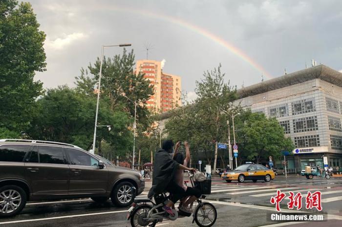 7月6日,一场暴雨过后,北京天空出现彩虹,吸引市民拍照。 中新社记者 盛佳鹏 摄