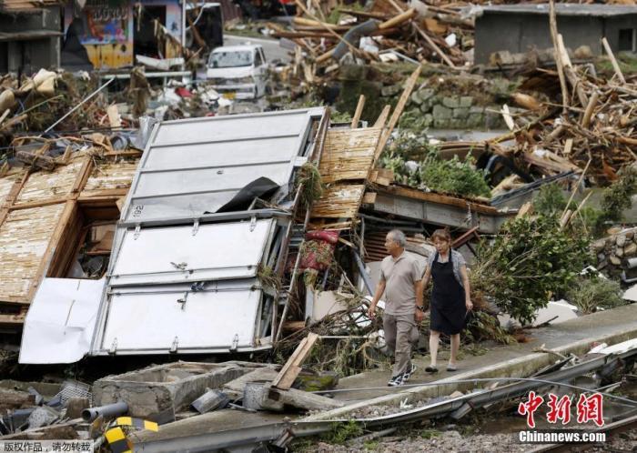 日本九州各地近日遭遇强降雨,图为熊本县一对夫妇走过被冲毁的房屋。