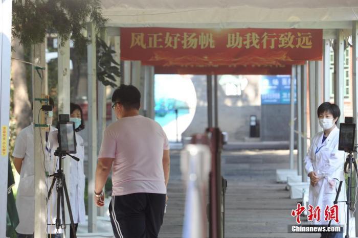 图为北京市第十三中学考点考生测体温后步入考场。中新网记者 李骏 摄