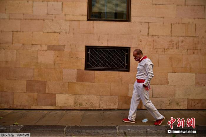 当地时间2020年7月7日,西班牙北部班普罗纳,今年的奔牛节被取消,一位戴着面罩的参赛者沿着圣佛明节奔牛的路线行走。