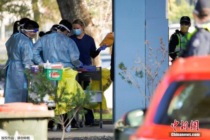 当地时间7月8日,澳大利亚墨尔本,为应对新冠状病毒病的爆发,工作人员在公共住宅大楼外参加简报会。