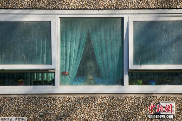 据报道,维州一夜激增191例新冠确诊病例,系疫情暴发以来该州单日新增新高。安德鲁斯敦促居民不要自我欺骗,佯装疫情危机已成过去。图为当地时间7月8日,澳大利亚墨尔本,一名居民从窗户向外看,这座公共住宅楼因应对新冠状病毒病的爆发而被锁起来。