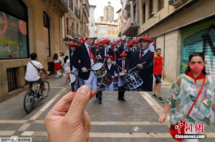 当地时间2020年7月7日,西班牙潘普洛纳,圣佛明节狂欢活动因疫情取消,摄影师拿着一张2019年7月拍摄的乐队在圣佛明节开幕式上演奏的照片,再现圣佛明节狂欢活动盛况。
