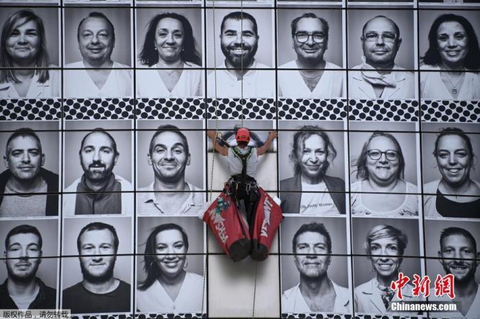 当地时间7月8日,法国巴黎,法国艺术家Jean Rene aka JR创作巨幅马赛克作品,由医护人员的肖像组成,以向医护人员致敬。该作品由专业登山运动员安装在巴士底歌剧院外。