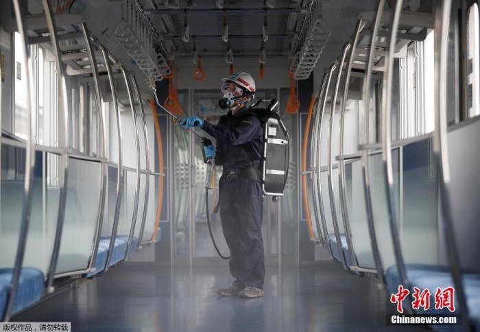 图为当地时间7月9日,日本东京,一名戴着防护面具和护目镜的东京地铁员工对车厢进行消毒。