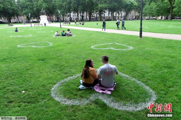 当地时间2020年7月8日,英国布里斯托尔,艺术家在皇后广场的草地上画出心形图案,敦促人们保持社交距离。
