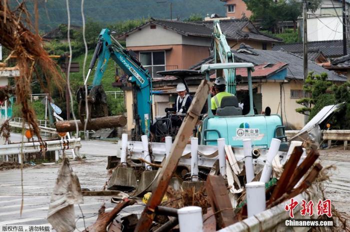当地时间7月9日,日本西南部熊本县熊本市,暴雨引发的洪水席卷熊村,工人们正在清除道路上的碎片。