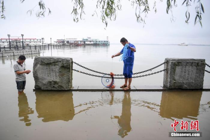 市民在岳阳巴陵广场的景观道捕鱼。 杨华峰 摄